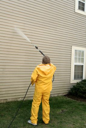 Pressure washing the siding of a house by Edgar's Handyman & Painting.